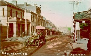 Glebe Point Road coloured postcard - strip shopping - tram tracks